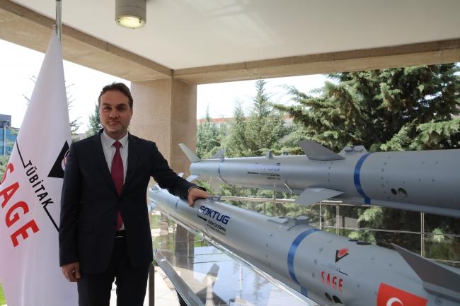 [TÜBİTAK SAGE Müdürü Gürcan Okumuş, Göktuğ projesindeki füzelerin önünde. Foto: AA]